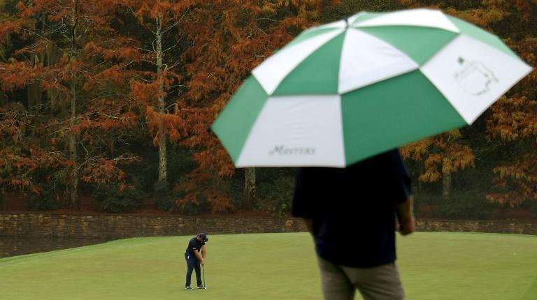 US Open winner Bryson DeChambeau putts on the 11th green at Augusta National on Wednesday while being watched in the rain on the eve of the 84th Masters