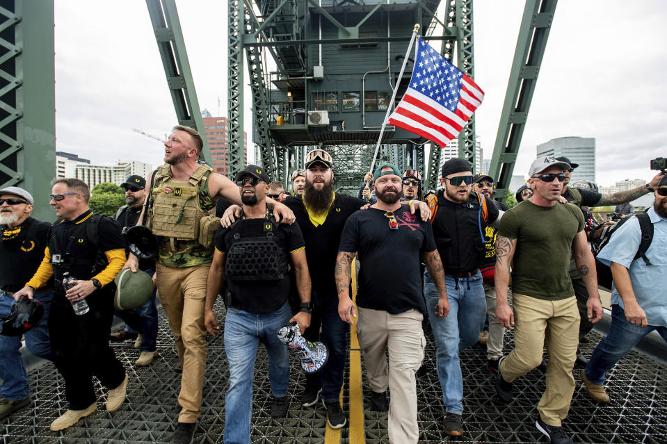 """FILE - In this Aug. 17, 2019 file photo organizer Joe Biggs, in green hat, and Proud Boys Chairman Enrique Tarrio, holding megaphone, march with members of the Proud Boys and other right-wing demonstrators march across the Hawthorne Bridge during a rally in Portland, Ore. Proud Boys """"thought leader"""" and organizer Joseph Biggs agreed to provide the FBI with information about """"Antifa networks"""" in Florida and elsewhere after an agent contacted him in late July 2020 and arranged to meet at a restaurant, Biggs' lawyer, J. Daniel Hull, wrote Monday, March 29, 2021, in a court filing. (AP Photo/Noah Berger,File)"""