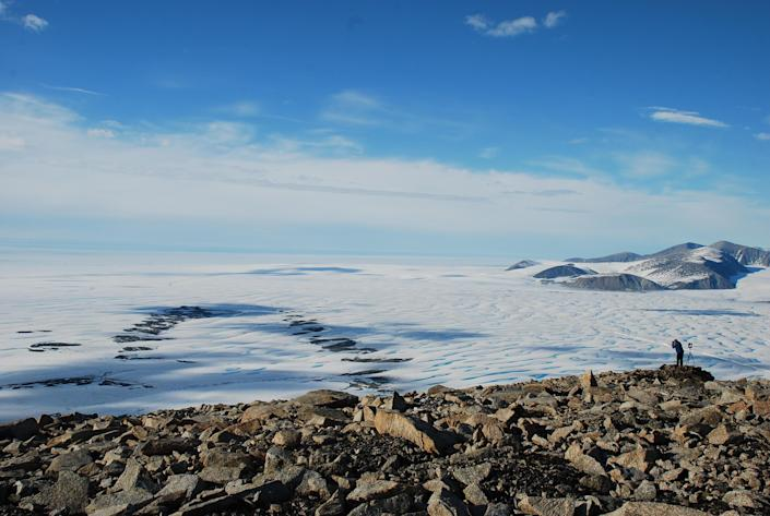 Luke Copland, University Research Chair in Glaciology, Department of Geography, University of Ottawa, overlooks the Milne Ice Shelf. Adrienne White, PhD, who took the photo, said the majority of the ice seen on the left side of the image is now gone. / Credit: Adrienne White, PhD