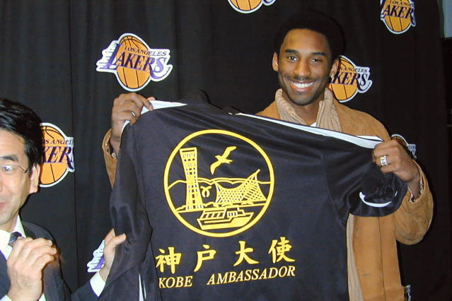 In this Dec. 14, 2001, photo, Kobe Bryant, then NBA player from the Los Angeles Lakers, poses with a jersey after being named the newest ambassador for the city of Kobe, Japan before a game against the Los Angeles Clippers at the Staples Center, in Los Angeles, Calif. Bryant died in a helicopter crash Sunday, Jan. 26, 2020. Tetsunori Tanimoto, an official at the Kobe Beef Marketing & Distribution Promotion Association, in Kobe, central Japan, expressed his deep condolences for Kobe Bryants death. He helped make Kobe Beef known throughout the world, Tanimoto said in a telephone interview with The Associated Press Monday. (Kyodo News via AP)