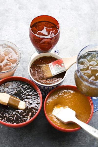 In this image taken on June 10, 2013, from top clockwise, recado rojo, tangy apricot barbecue sauce, and balsamic strawberry jalapeno barbecue sauce are shown with cocktails in Concord, N.H. (AP Photo/Matthew Mead)