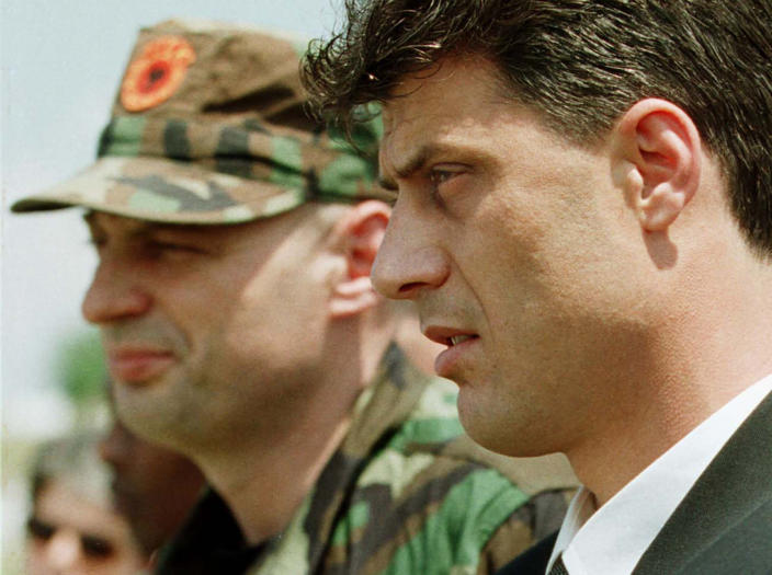 FILE - In this Friday Aug. 6, 1999 file photo, Kosovo Liberation Army leader Hashim Thaci, right, and KLA general commander Agim Ceku, left, attend a memorial ceremony for ethnic Albanian leader Fehmi Agani in Pristina, in the Yugoslav province of Kosovo. Kosovo's President Hashim Thaci, a guerrilla leader during Kosovo's war for independence from Serbia in the late 1990s, resigned on Thursday Nov. 5, 2020 and will face charges for war crimes and crimes against humanity at a special court based in The Hague. (AP Photo/Lefteris Pitarakis, File)