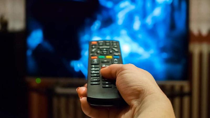 Lady holding remote control pointed towards a TV
