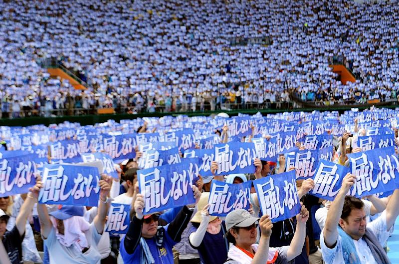 """An estimated 35,000 protesters raise placards saying """"Do not yield to authority"""" during a rally to protest against a controversial US airbase in Naha in Japan's southern island of Okinawa on May 17, 2015 (AFP Photo/)"""