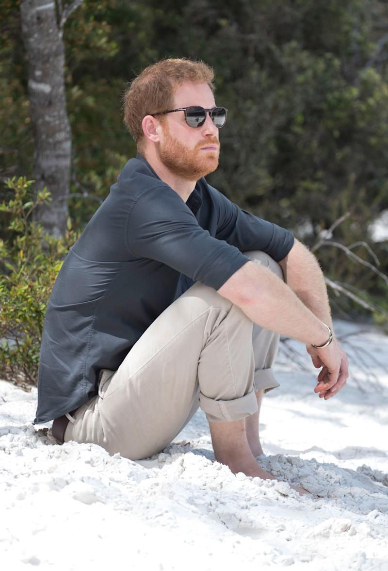 Prince Harry sitting on a beach