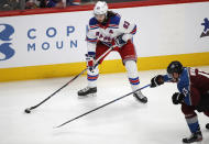 New York Rangers center Mika Zibanejad, back, shoots the puck as Colorado Avalanche right wing Valeri Nichushkin defends during the first period of an NHL hockey game Wednesday, March 11, 2020, in Denver. (AP Photo/David Zalubowski)