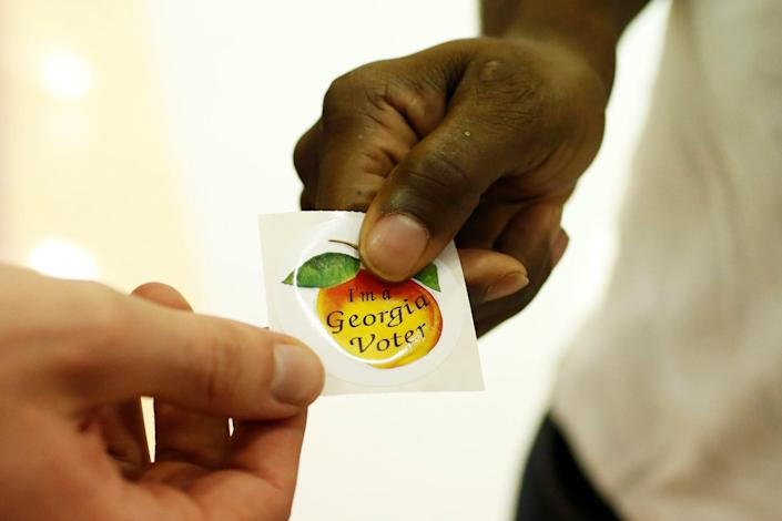 """A voter picks up an """"I'm a Georgia Voter"""" sticker after voting at Clarke Central High School in Athens on Tuesday, Nov. 3."""