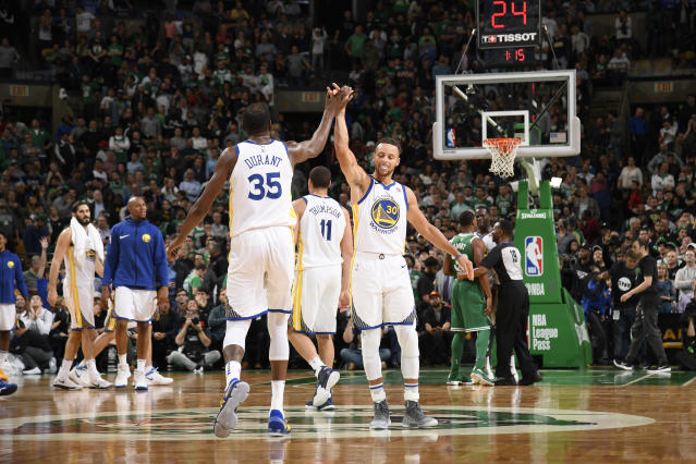 """<a class=""""link rapid-noclick-resp"""" href=""""/nba/players/4244/"""" data-ylk=""""slk:Kevin Durant"""">Kevin Durant</a> and <a class=""""link rapid-noclick-resp"""" href=""""/nba/players/4612/"""" data-ylk=""""slk:Stephen Curry"""">Stephen Curry</a> high-five during the first half of the Warriors' loss to the Celtics on Thursday. (Getty)"""
