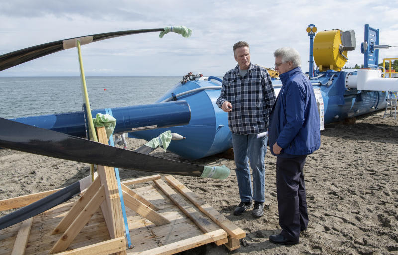 In this Tuesday, July 16, 2019, photo released by the Alaska Governor's office, Gov. Mike Dunleavy, left, talks with ORPC CEO, Co-Founder, and Chairman Chris Sauer in front of a Riv-Gen Power System turbine on the bank of the Kvichak River in Igiugig, Alaska. A tiny Alaska Native village is adopting an emerging technology to transform the power of a local river into a renewable energy source. (Austin McDaniel/Alaska Governor's Office via AP)