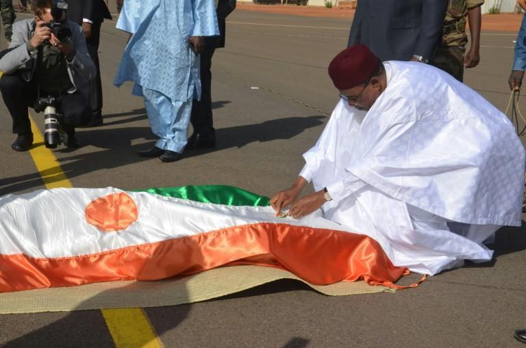 Mourning: Issoufou bows before the remains of soldiers killed in a jihadist attack on a base in Tillaberi, western Niger, in December 2019. Seventy-one died