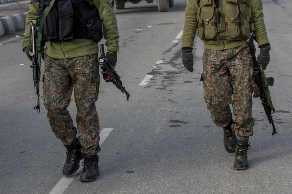 Indian army soldiers walk towards the site of a gun battle on the outskirts of Srinagar, Indian controlled Kashmir, Wednesday, Dec. 30, 2020. A gun battle between rebels and government forces overnight killed three rebels on the outskirts of Srinagar on Wednesday, officials said. (AP Photo/ Dar Yasin)
