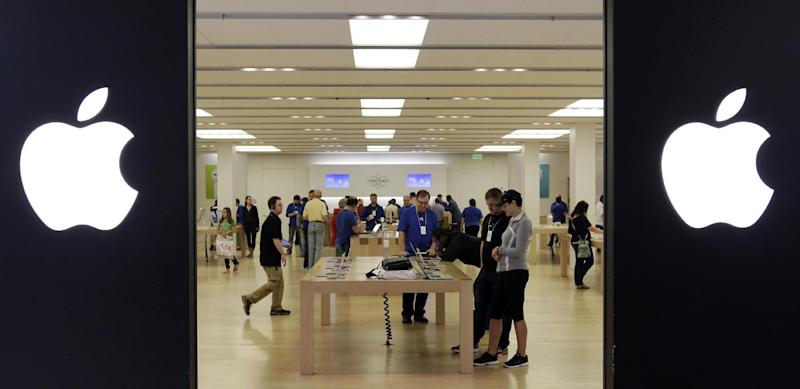 FILE - In this Friday, Oct, 26, 2012, file photo, people shop at an Apple store inside a mall in Cheektowaga, N.Y. Apple Inc. paid a rate of only 1.9 percent income tax on its earnings outside the U.S. in its latest fiscal year, a regulatory filing by the company shows. The world's most valuable company paid $713 million in tax on foreign earnings of $36.8 billion in the fiscal year ended Sept. 29, according to the financial statement filed on Oct. 31. (AP Photo/David Duprey, File)