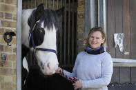 General manager Naomi Howgate poses for photo with Joe, at Ebony Horse Club in Brixton, south London, Sunday, April 18, 2021. In the midst of south London's hustle and bustle, only a 10-minute walk from a subway station, is a school where children are encouraged to horse around. The Ebony Horse Club provides 140 rides per week to children in the local community offering them the opportunity to learn important life skills along with horseback riding. (AP Photo/Kirsty Wigglesworth)