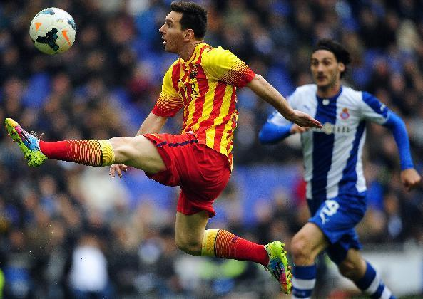FC Barcelona's Lionel Messi, left, duels for the ball against Espanyol's Diego Colotto during a Spanish La Liga soccer match against Espanyol at Cornella-El Prat stadium in Cornella Llobregat, Spain, Saturday, March 29, 2014. (AP Photo/Manu Fernandez)