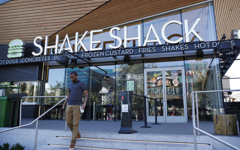 FILE - In this April 15, 2015, file photo, a man walks out of a Shake Shack in front of the New York-New York hotel and casino in Las Vegas. Shake Shack reports financial results Wednesday, Aug. 10, 2016. (AP Photo/John Locher, File)