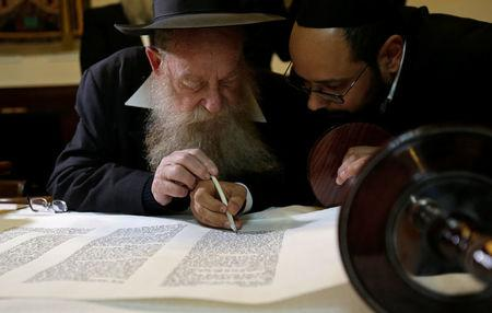Members of the Czech Jewish Community write final words in a new Torah scroll during a ceremony in the medieval Old-New Synagogue in Prague