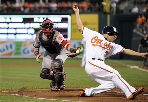 Baltimore Orioles' Omar Quintanilla, right, slides by after he was tagged out by Boston Red Sox catcher Jarrod Saltalamacchia, left, on a single by J.J. Hardy during the second inning of a baseball game on Thursday, Aug. 16, 2012, in Baltimore. (AP Photo/Nick Wass)