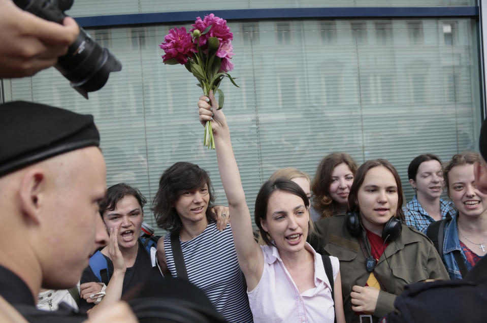 "A police officer watches gay rights activists gather near the State Duma, Russia's lower parliament chamber, in Moscow, Russia, Tuesday, June 11, 2013. Protesters attempted to rally outside the Russian State Duma before what is expected to be a final vote on the bill banning ""propaganda of nontraditional sexual relations."" More than two dozen activists were detained in Moscow on Tuesday as they were protesting a bill that stigmatizes the gay community and bans the giving of information about homosexuality to children. (AP Photo/Ivan Sekretarev)"