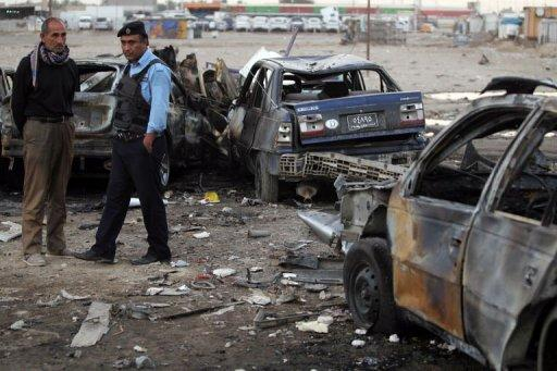 An Iraqi policeman and civilian inspect the site of a car bomb attack in Baghdad's Sadr City district, on April 16, 2013