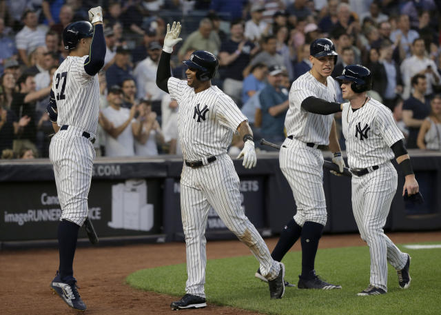 New York Yankees' Aaron Hicks, second from left, celebrates his two-run home run with teammates Giancarlo Stanton, left, Aaron Judge, second from right, and Clint Frazier during the fifth inning of a MLB baseball game against the Seattle Mariners at Yankee Stadium Tuesday, June 19, 2018, in New York. (AP Photo/Seth Wenig)