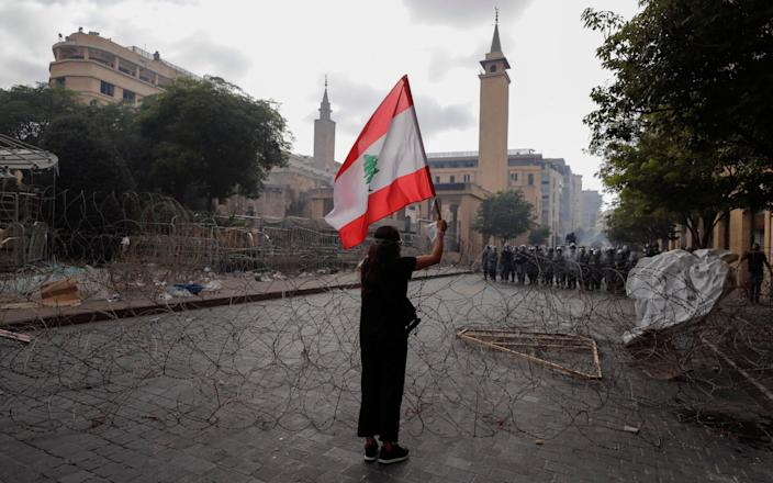 A woman waves the Lebanese flag during a protest against the political elites - AP