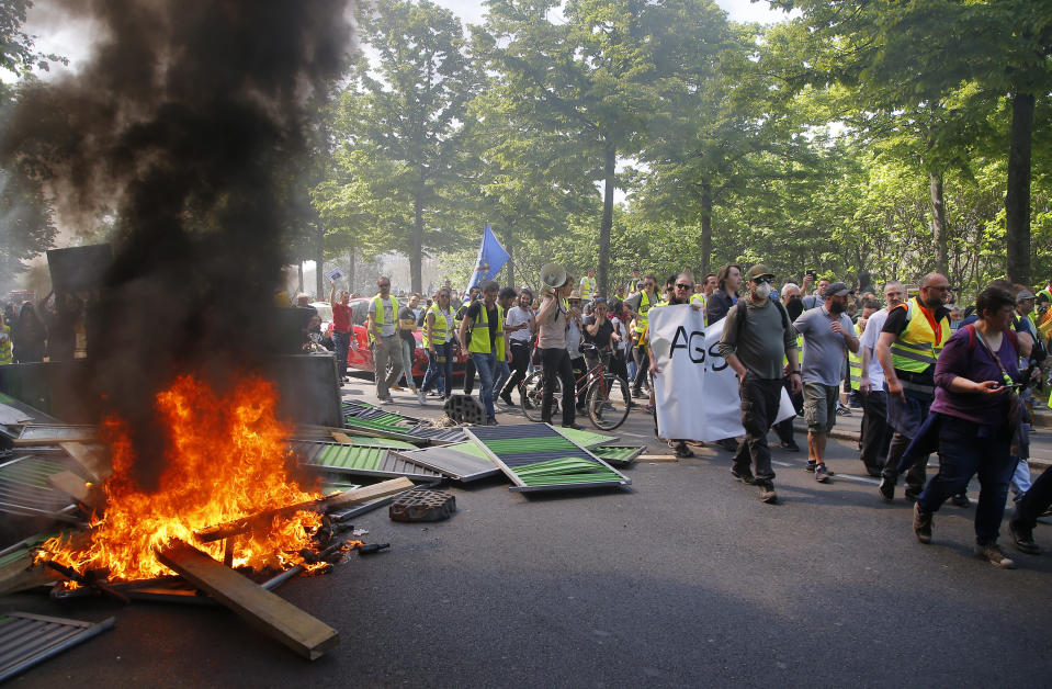 Protestors march by a burning pile of wood during a yellow vest demonstration in Paris, Saturday, April 20, 2019. French yellow vest protesters are marching anew to remind the government that rebuilding the fire-ravaged Notre Dame Cathedral isn't the only problem the nation needs to solve. (AP Photo/Michel Euler)