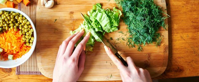 Top view of hands cutting lettuce