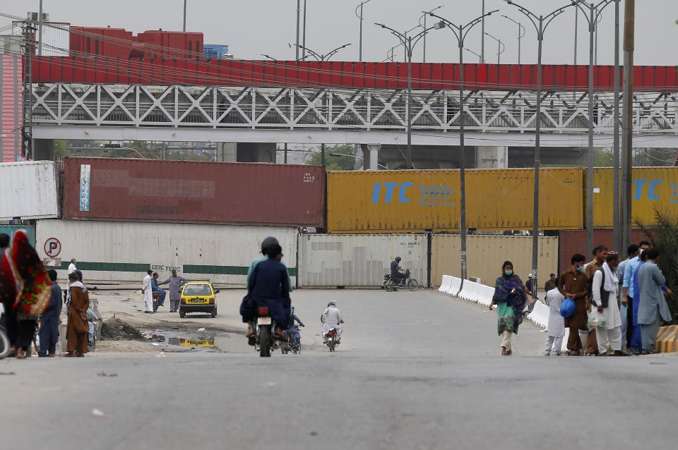 Shipping containers are placed by authorities to block a road leading to the capital as a security measure on the possible anti-France protest march by a banned radical Islamists Tehreek-e-Labaik Pakistan party, in Rawalpindi, Pakistan, Tuesday, April 20, 2021. Pakistan's Parliament is expected to consider a resolution on Tuesday about whether the French envoy should be expelled over the publication of controversial cartoons depicting Islam's Prophet, testing whether the government gives in to threats from radical Islamists. (AP Photo/Anjum Naveed)