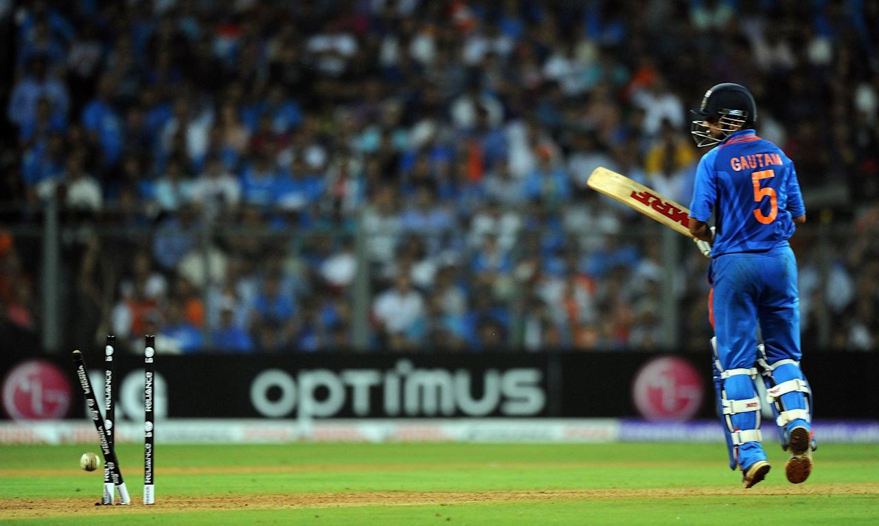 Indian batsman Gautam Gambhir looks back at his shattered stumps after being dismissed during the ICC Cricket World Cup final between India and Sri Lanka at The Wankhede Stadium in Mumbai on April 2, 2011. AFP PHOTO/Indranil MUKHERJEE (Photo credit should read INDRANIL MUKHERJEE/AFP/Getty Images)