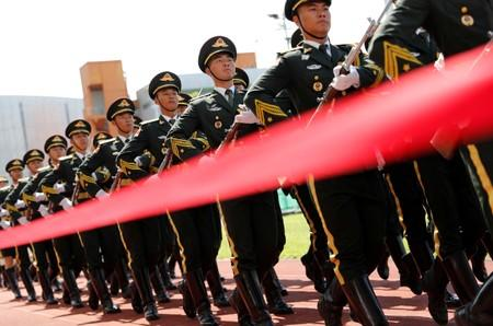 Members of People's Liberation Army (PLA) honour guards march for the flag raising ceremony during an open day of Stonecutters Island naval base, in Hong Kong