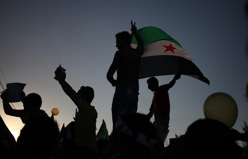Syrian demonstrators wave the Syrian revolutionary flag and victory signs during a protest in front of the Syrian embassy in Amman, Jordan, Friday, Aug. 23, 2013. Anti-government activists accused the Syrian regime of carrying out a toxic gas attack that is thought to have killed at least 100 people, including many children as they slept, during intense artillery and rocket barrages Wednesday on the eastern suburbs of Damascus that are part of a government offensive in the area. (AP Photo/Mohammad Hannon)