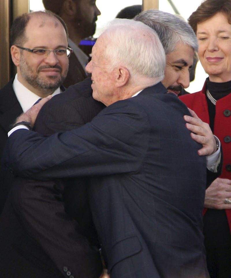 Hamas leader Khaled Mashaal, left, embraces former U.S. President Jimmy Carter as former Irish President Mary Robinson, right, looks on in Damascus, Syria, Tuesday, Oct. 19, 2010. Following a meeting with Syrian President Bashar Assad, the Elders, an independent group founded in 2007 to support worldwide peace-making and challenge injustice, headed into a meeting with Mashaal. The Elders, who combined Carter, Robinson, former Algerian Foreign Minister Lakhdar Brahimi and Indian activist Ela Bhatt, are on a regional tour to promote peace talks between Israel and the Arabs. (AP Photo/Bassem Tellawi)