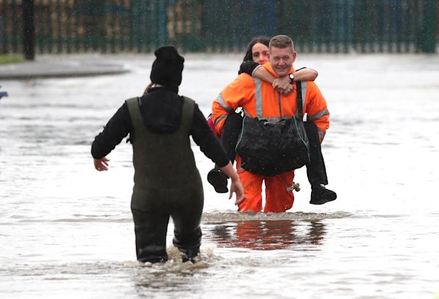 A man in high visibility overalls carries a woman through floodwater in Doncaster, Yorkshire, as parts of England endured a month's worth of rain in 24 hours (PA)