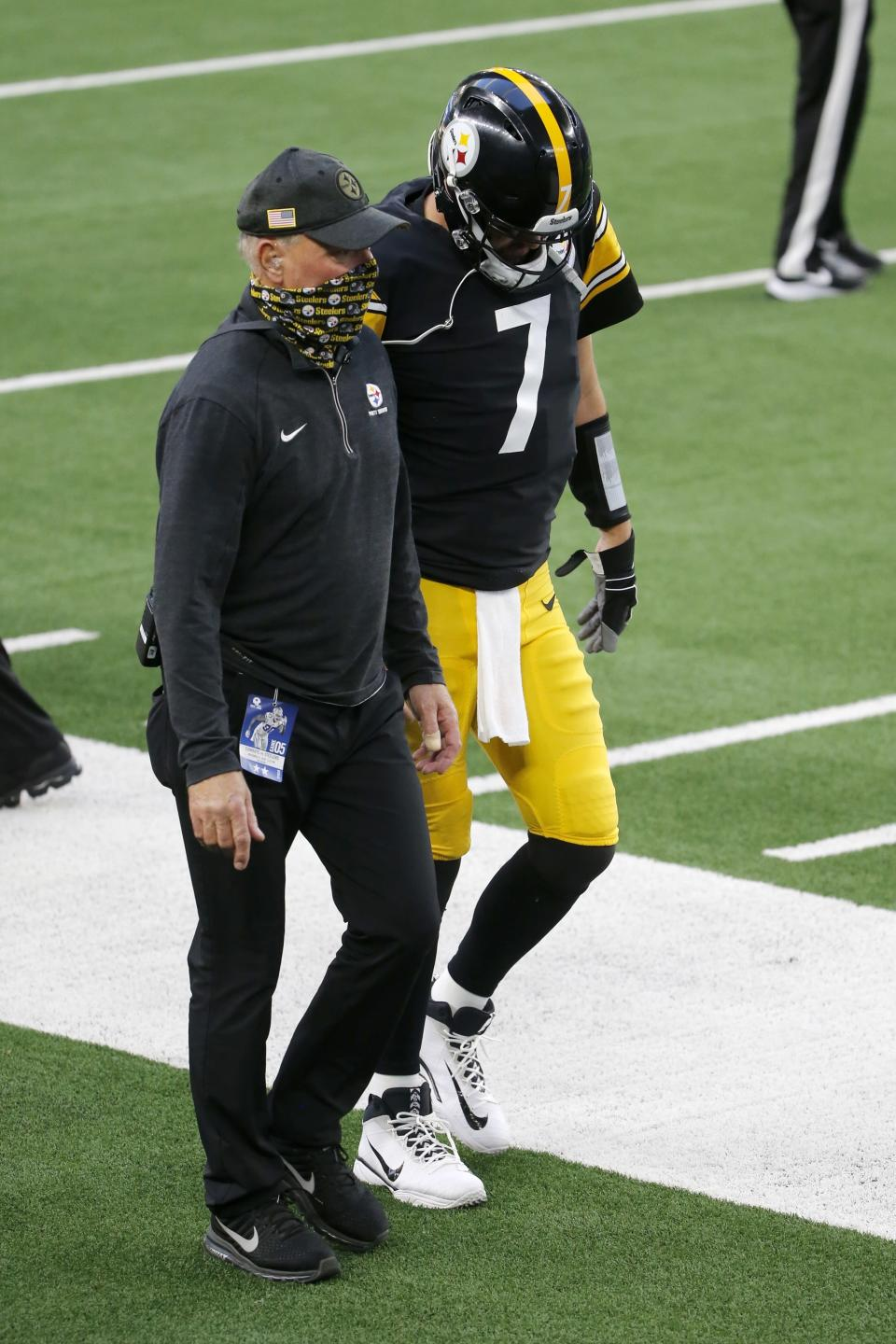 A member of the staff escorts Pittsburgh Steelers quarterback Ben Roethlisberger (7) to the locker room before the end of the first half of an NFL football game against the Dallas Cowboys in Arlington, Texas, Sunday, Nov. 8, 2020. (AP Photo/Michael Ainsworth)
