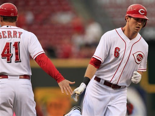 Cincinnati Reds center fielder Drew Stubbs (6) is congratulated by third base coach Mark Berry (41) after hitting a solo home run off Atlanta Braves starting pitcher Mike Minor in the first inning of a baseball game, Monday, May 21, 2012, in Cincinnati. (AP Photo/Al Behrman)