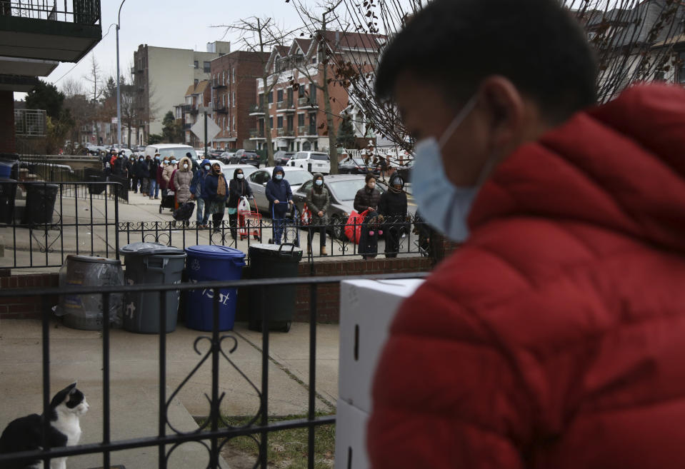 A line of people stretches for two blocks outside the United Sherpa Association's weekly food pantry on Friday, Jan. 15, 2021, in the Queens borough of New York. The pantry began in April with a focus on the Nepalese community, international students and families living in the country without permission. (AP Photo/Jessie Wardarski)