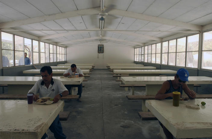 FILE - In this May 12, 2005 file photo, inmates have their meal in the mess hall at the Islas Marias federal prison island, located 90 miles south of Mazatlan, Mexico. President Andres Manuel Lopez Obrador said on Monday, Feb. 18, 2019 that he will close the famed island penal colony and will have it converted into a cultural and environmental education center. (AP Photo/Eduardo Verdugo, File)
