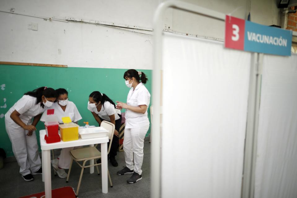Nurses read instructions for injecting doses of the Sputnik V COVID-19 vaccine at a Bernal public school, on the outskirts of Buenos Aires, Argentina, Thursday, Feb. 18, 2021, as the country begins to vaccinate healthcare workers against the new coronavirus. (AP Photo/Natacha Pisarenko)