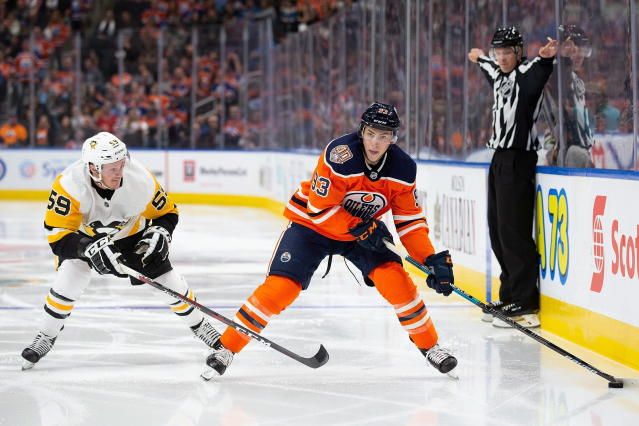 Edmonton Oilers' Ryan Nugent-Hopkins (93) keeps the puck away from Pittsburgh Penguins' Jake Guentzel (59) during the second period of an NHL hockey game, in Edmonton, Alberta, Tuesday, Oct. 23, 2018. (Codie McLachlan/The Canadian Press via AP)