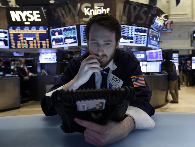 Trader Timothy Pastina works on his handheld device, on the floor of the New York Stock Exchange, Wednesday, June 19, 2013. Stocks edged lower in early trading on Wall Street Wednesday as investors waited for word from the Federal Reserve. (AP Photo/Richard Drew)