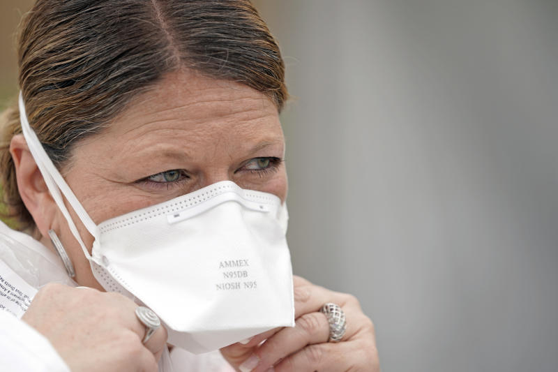 Nurse Yvette Laugere adjusts her N95 mask while working at a newly opened free Covid-19 testing site operated by United Memorial Medical Center Thursday, April 2, 2020, in Houston. The new coronavirus causes mild or moderate symptoms for most people, but for some, especially older adults and people with existing health problems, it can cause more severe illness or death. (AP Photo/David J. Phillip)