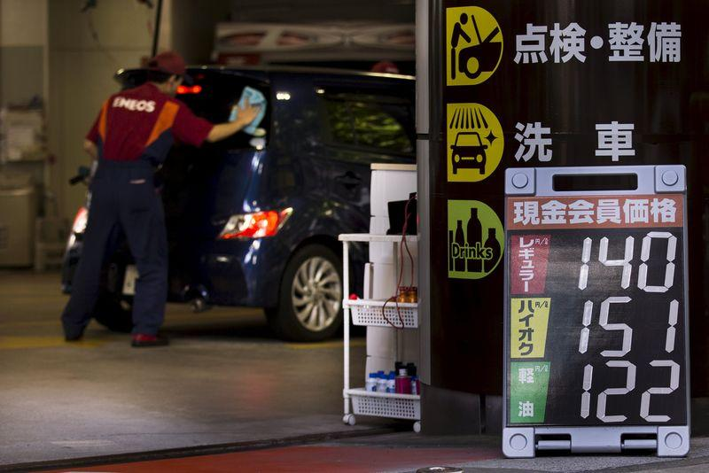 Attendant cleans the window of a car near a sign displaying the petrol station's current fuel prices in yen in Tokyo