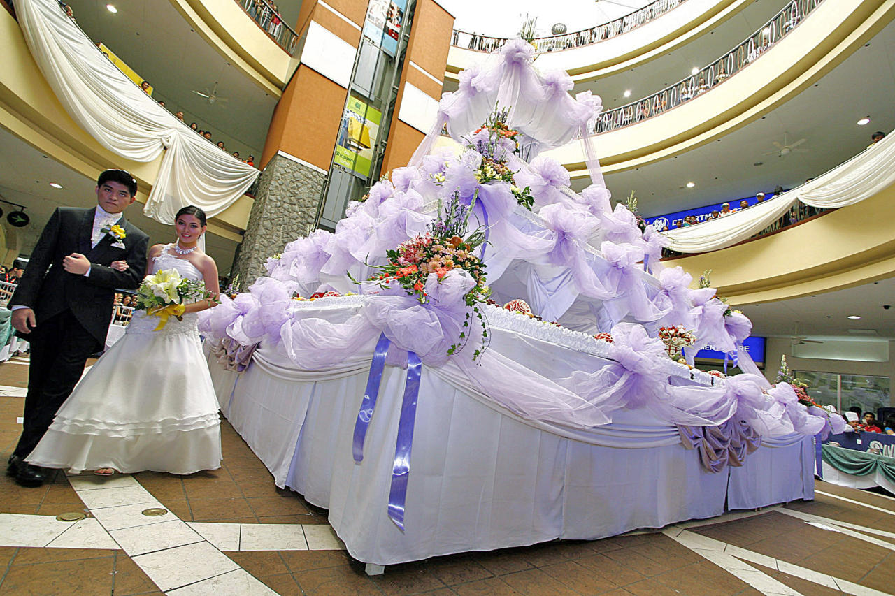 LARGER THAN LIFE - Models in wedding attire pause beside a huge chocolate wedding cake during the opening of the Hotel, Restaurant and Tourism Week in Baguio City Thursday. The 28-feet tall, 24.5-feet wide cake weighs 3 tons and is supposedly enough for 10,000 people. (NPPA Images)
