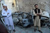 Aimal Ahmadi (R), brother of Ezmarai Ahmadi, who was one of 10 people killed in a US drone strike in Kabul that the US now says was a mistake, stands next to the wreckage of a vehicle destroyed in the attack (AFP/Hoshang Hashimi)