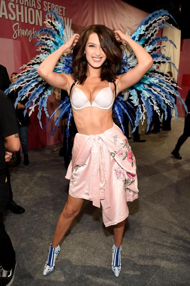 Before hitting the runway in her wings, Hadid had some fun backstage with photographers. (Photo: Getty Images)