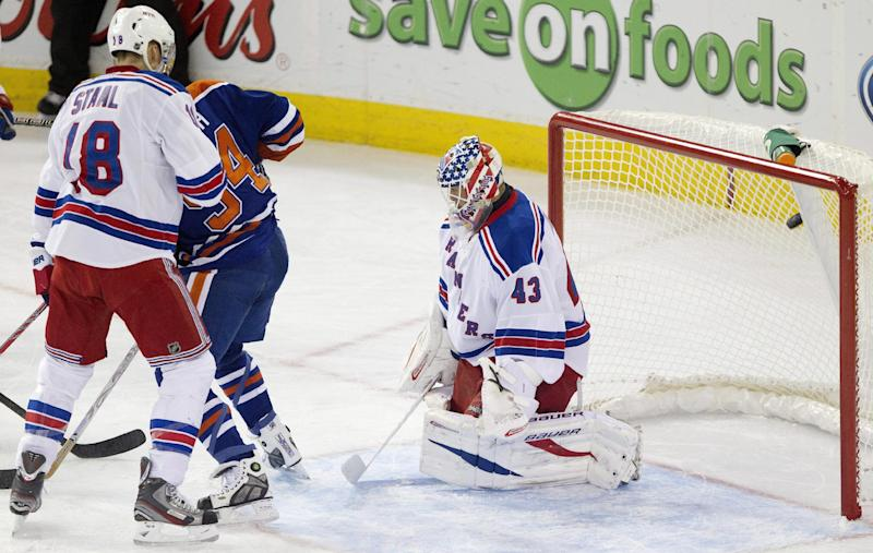 New York Rangers goalie Martin Biron (43) is scored on as teammate Marc Staal (18) and Edmonton Oilers' Ryan Smyth (94) battle in front of the net during the first period of an NHL hockey preseason game, Tuesday, Sept. 24, 2013, in Edmonton, Alberta. (AP Photo/The Canadian Press, Jason Franson)