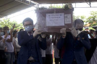 Colleagues carry the coffin containing the remains of Mia Tresetyani, a victim of the crash of Sriwijaya Air flight SJ-182 during her burial in Denpasar, Bali, Indonesia on Thursday, Jan. 21, 2021. The Indonesian leader on Wednesday reassured relatives of the passengers killed when the plane nosedived into the Java Sea that compensation is paid to family members struggled with grief. (AP Photo/Firdia Lisnawati)