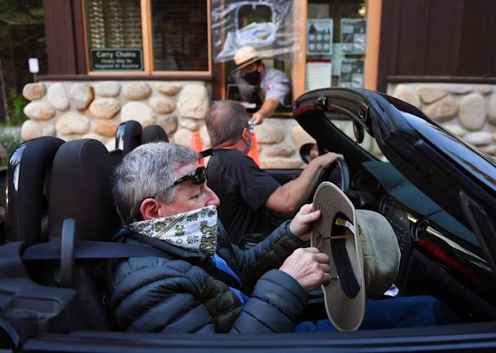 Richard Trotter, foreground, fixes his hat as a ranger hands his son Chad Trotter information at the south entrance of Yosemite National Park as it reopens after a historic closure Thursday, June 11, 2020. The Trotters said they drove 12 hours from Prescott, AZ. just for the event.