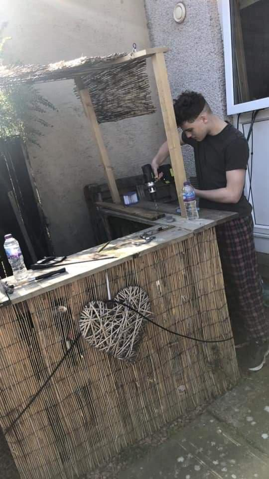 Son, Josh, put his woodwork skills to good use making the tiki bar. (SWNS)