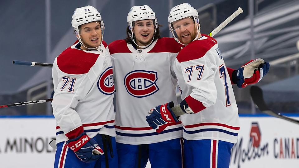 Canadiens rookie Alexander Romanov celebrates with teammates Jake Evans (left) and Brett Kulak (right) after scoring his first NHL goal against the Edmonton Oilers. (Photo by Codie McLachlan/Getty Images)